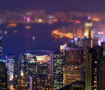 40108928 - night aerial view panorama of hong kong skyline and victoria harbor. tilt shift effect. abstract futuristic cityscape with modern skyscrapers
